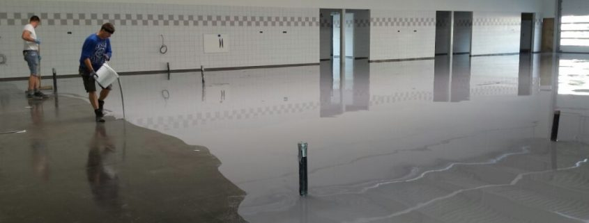 Concrete coating being applied on a concrete floor