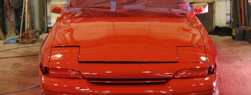 red vehicle refinish paint being applied on a masked car